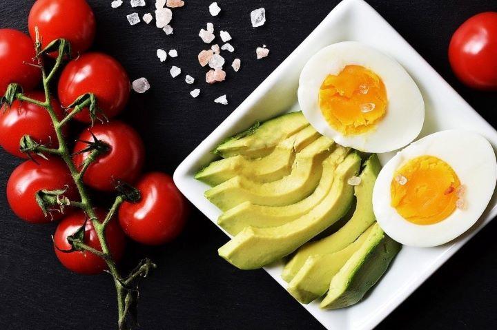 Авокадо и вареное яйцо в белой тарелке, рядом помидоры