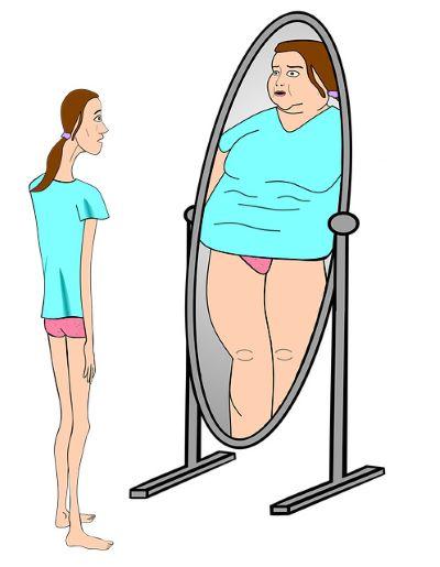 Девушка смотрит в зеркало на свое отражение
