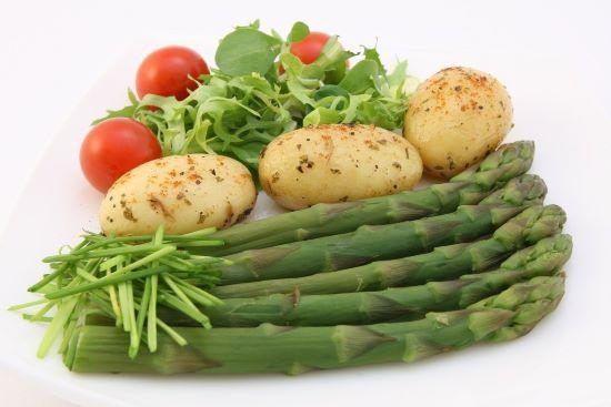 Спаржа, картофель, помидоры и зелень на тарелке